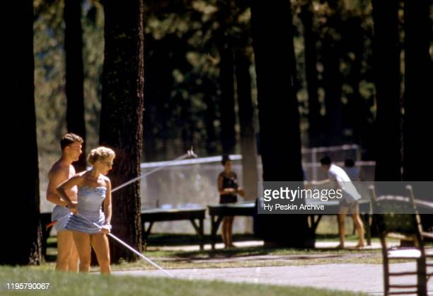 General view as a couple plays shuffleboard wearing bathing suits circa 1958
