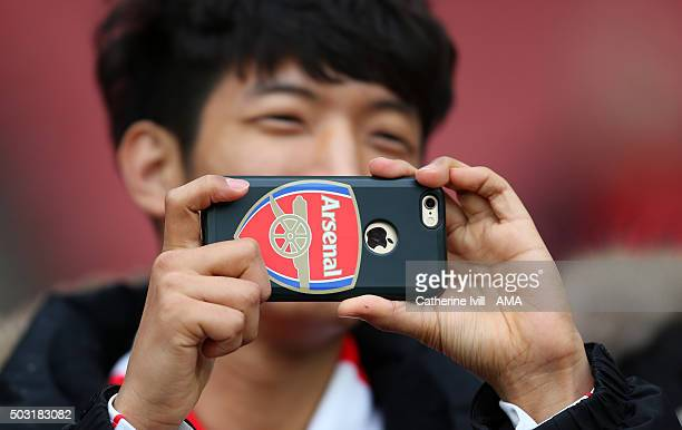 General view as a fan takes a photo using his phone with an Arsenal cover on before the Barclays Premier League match between Arsenal and Newcastle...