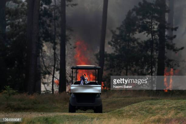 General view as a golf buggy is seen as course staff work to stop a fire which spread from Cobham heath over to the 9th and 10th holes as smoke is...