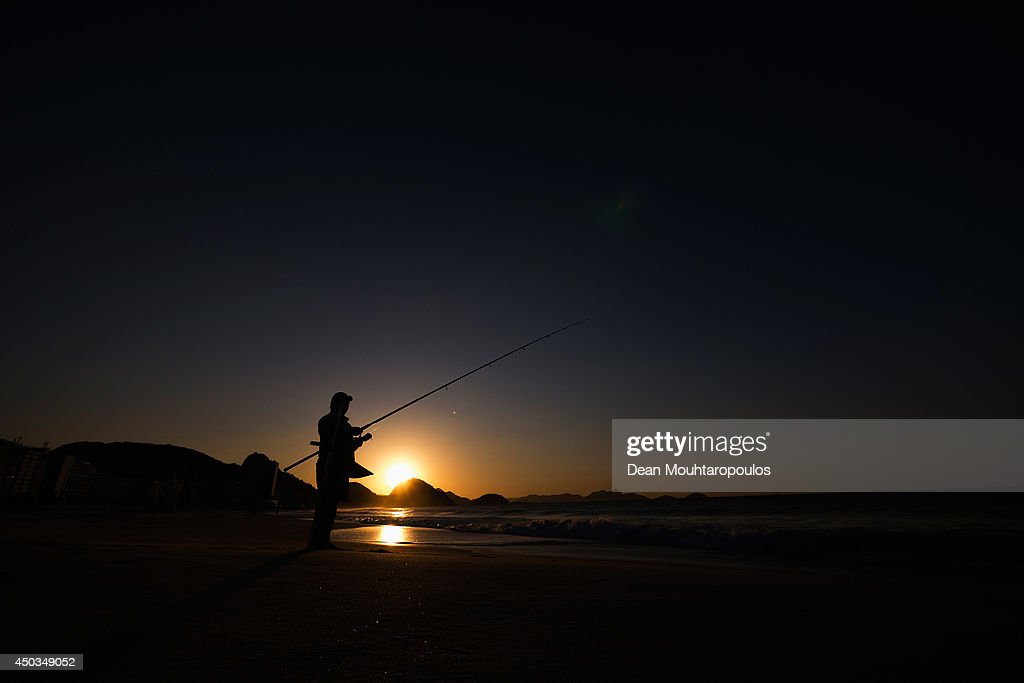 A general view as a local man fishes on the Copacabana Beach as the sun rises prior to the 2014 FIFA World Cup on June 9, 2014 in Rio de Janeiro, Brazil.