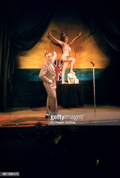 General view as a man on stage points at a naked woman during a peep show circa February 1958