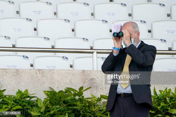A general view as a press member keeps an eye on matters with empty seating behind at Goodwood Racecourse on July 28 2020 in Chichester England...