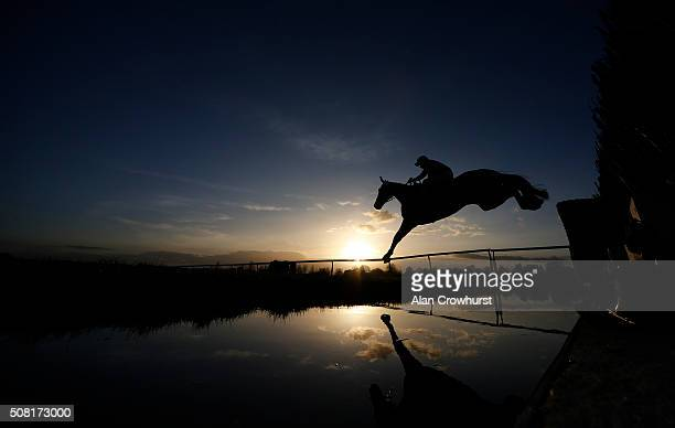 A general view as a runner clears the water jump in The Running Hare Handicap Steeple Chase as the sun begins to set at Leicester racecourse on...