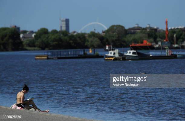 General view as a woman reads a book in the sunshine on the bank of the River Thames on May 20, 2020 in the Putney area of London, England. The...