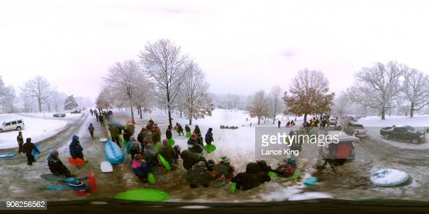 A general view as dozens of people gather to sled at Dorothea Dix Park during a snow storm on January 17 2018 in Raleigh North Carolina North...