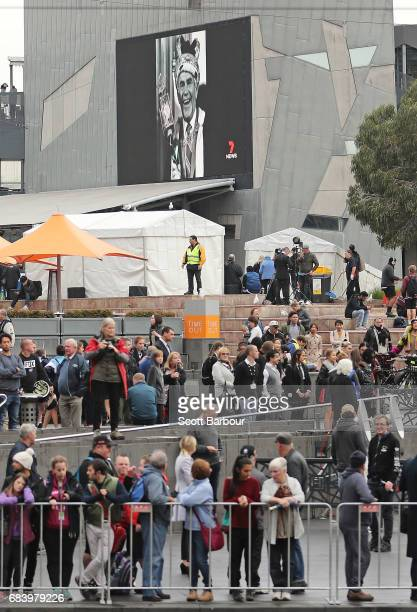 A general view as images of Lou Richards are shown on the large screen at Federation Square as people look on during the Lou Richards State Funeral...