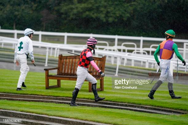 General view as jockeys make their way to the parade ring for the first race of the evening at Sandown Park on August 05, 2021 in Esher, England.
