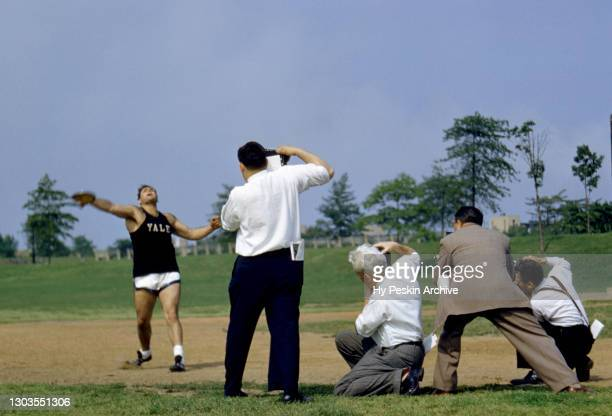 General view as photographers gather around a collegiate competitor from the University of Yale who throws his discus during the IC4A Track and Field...