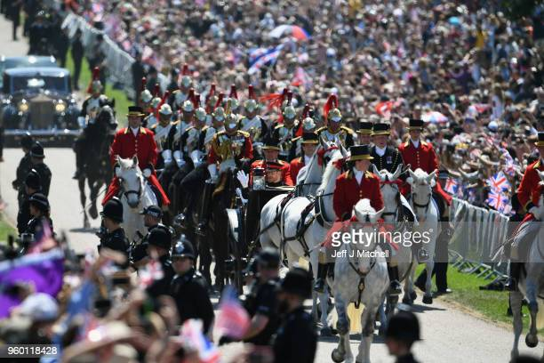 A general view as Prince Harry Duke of Sussex and Meghan Duchess of Sussex leave Windsor Castle in the Ascot Landau carriage during a procession...