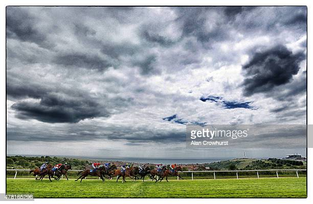 A general view as runners make their way towards the grandstand and finish in The Frosts4Cars Handicap at Brighton racecourse on June 23 2015 in...