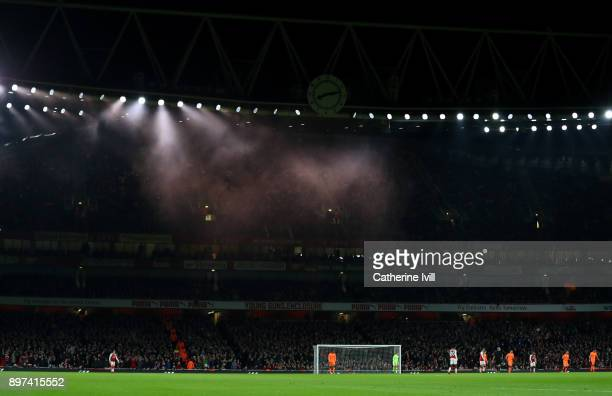 General view as Smoke from a flare can be seen in the floodlights during the Premier League match between Arsenal and Liverpool at Emirates Stadium...