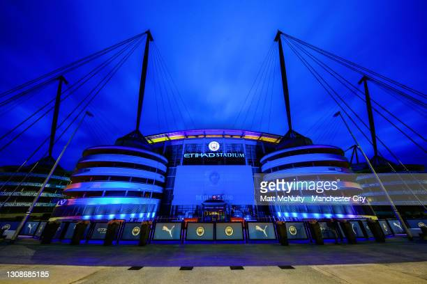 General view as the Etihad Stadium is lit up with blue lights as a memorial to mark one year since the first national lockdown due to the coronavirus...