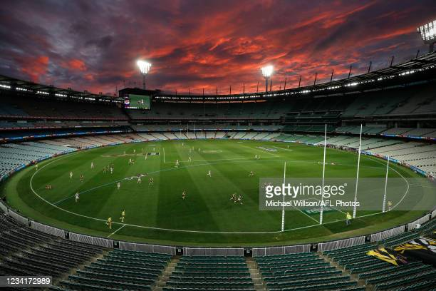 General view as the sun sets during the 2021 AFL Round 19 match between the Geelong Cats and the Richmond Tigers at the Melbourne Cricket Ground on...