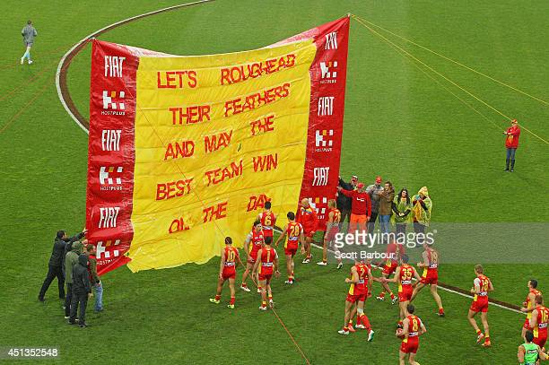 A general view as the Suns run through their banner during the round 15 AFL match between the Hawthorn Hawks and the Gold Coast Suns at Aurora...