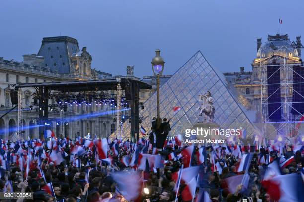 A general view as voters are waving flags during Emmanuel Macron speech as he celebrates his Presidential election victory At Le Louvre In Paris on...