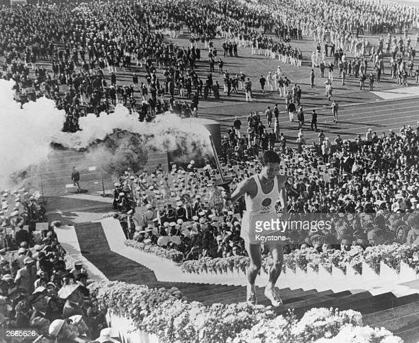 General view as Yoshinori Sakai, a student born in Hiroshima on the day the first atomic bomb devastated the city, carries the torch up the stairs to...