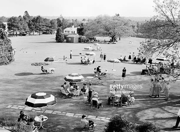 A general view from the back of the clubhouse overlooking patrons enjoying the patio area during the 1951 Masters Tournament at Augusta National Golf...