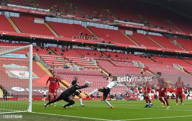 General view inside the empty stadium is pictured as Liverpool's Brazilian goalkeeper Alisson Becker saves a shot from Fulham's Nigerian striker Josh...