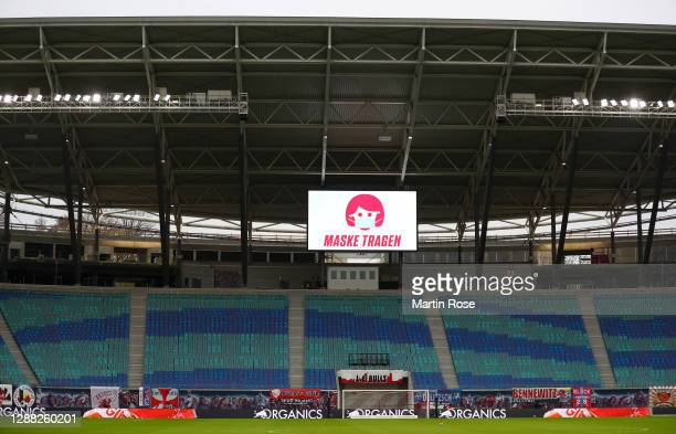 General view inside the stadium as the big screen displays a message urging people to wear a mask prior to the Bundesliga match between RB Leipzig...