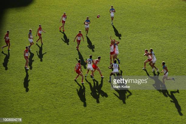 Jarrod Witts and Alex Sexton of the Suns compete for the ball with Callum Sinclair of the Swans during the round 18 AFL match between the Sydney...