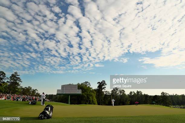 A general view is seen as Patrick Reed of the United States lines up a putt on the 18th green as Rory McIlroy of Northern Ireland looks on during the...