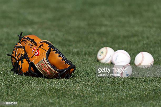 General view of a baseball glove and baseball on a grassy field before the game between the Oakland Athletics and the Toronto Blue Jays at Oco...