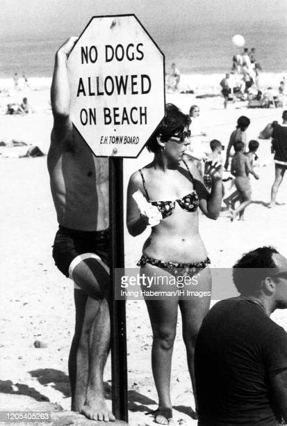 General view of a couple in their bathing suits stand next to a sign that reads No Dogs Allowed On Beach circa 1940's in East Hampton New York