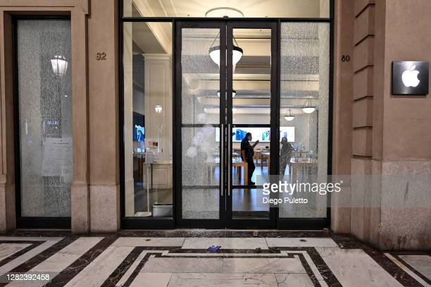 A general view of a damaged Apple store front as protesters gather during an anti government demonstration on October 26 2020 in Turin Italy...
