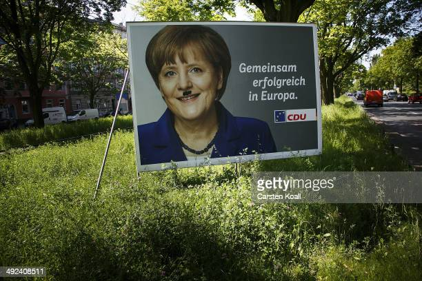 A general view of a defaced election campaign billboard for European Union parliamentary elections featuring German Chancellor and Chairwoman of the...