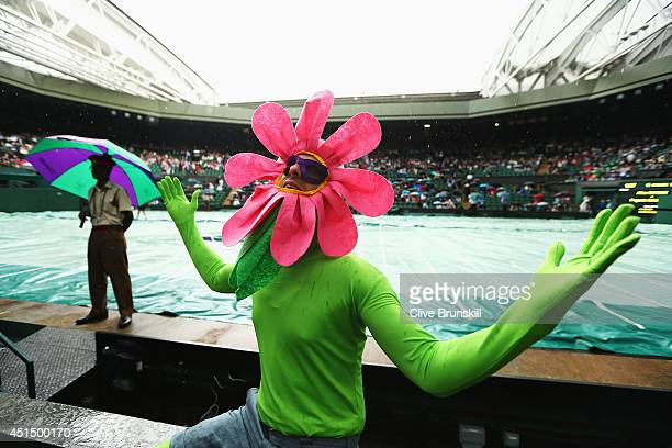 General view of a fan in fancy dress on Centre court as plays is suspending because of rain on day seven of the Wimbledon Lawn Tennis Championships...