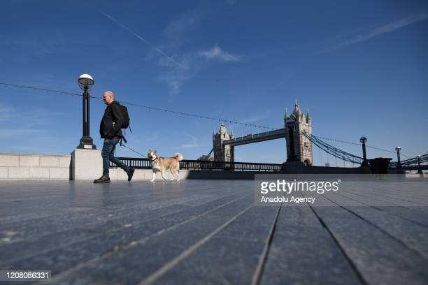 A general view of a man walking a dog in London Bridge on March 24 2020 in London England British Prime Minister Boris Johnson announced strict...