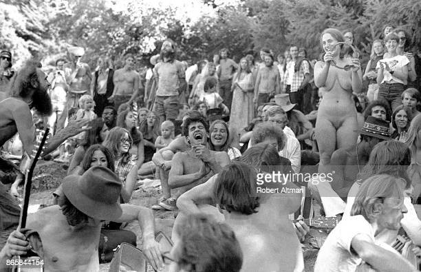 General view of a naked woman with a group of people as she holds a Tambourine on August 30 1969 at Mt Tamalpais in San Francisco California