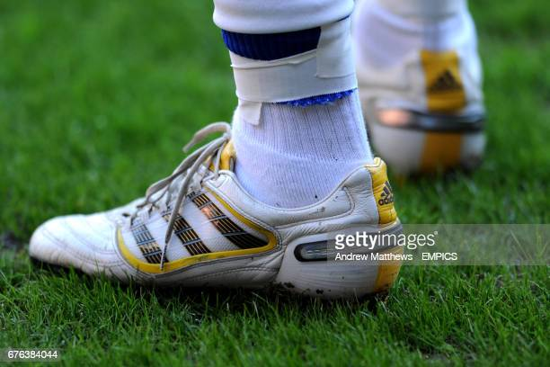 General view of a pair of white adidas predator football boots with yellow trim as worm by a Queens Park Rangers player