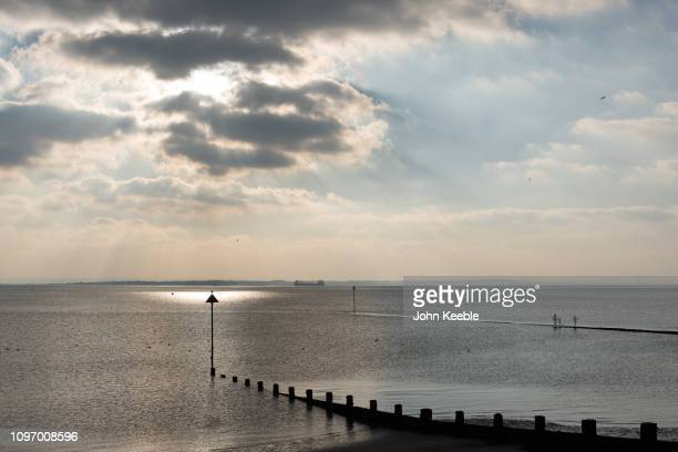 A general view of a parent and two small children walking out to sea on a jetty as the sun begins to set on January 20 2019 at Southend on Sea Essex...