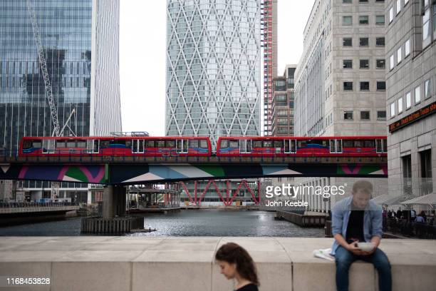 General view of a person eating lunch in Canary Wharf as a Docklands Light Railway train passes by on August 06, 2019 in London, England.