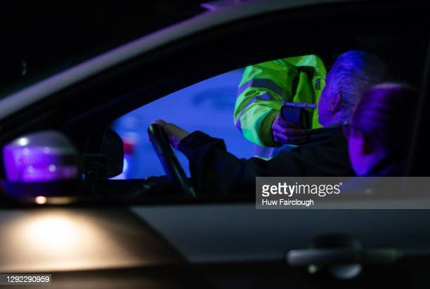 General view of a Police Officer administering a breath test when conducting vehicle checks with regards to compliance for drink driving, vehicle...