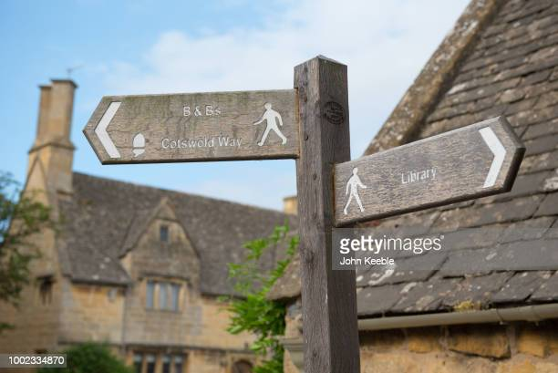 A general view of a public footpath sign pointing towards BBs Cotswold Way and the library in the Cotswolds on July 10 2018 in Broadway England