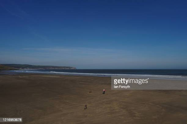 General view of a resident of Whitby walks as she her dogs on the beach while visitors observe the guidelines during the Coronavirus pandemic...