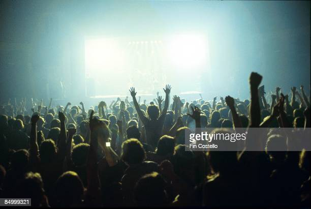A general view of a rock concert taken from the back fo a venue showing the audience in silhouette raising their arms and cheering with bright lights...