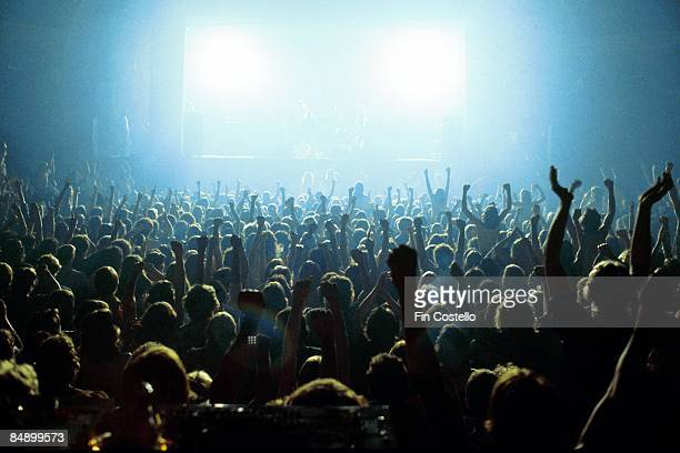 A general view of a rock concert taken from the back of the venue above the crowds showing the audience in silhouette raising their arms and cheering...