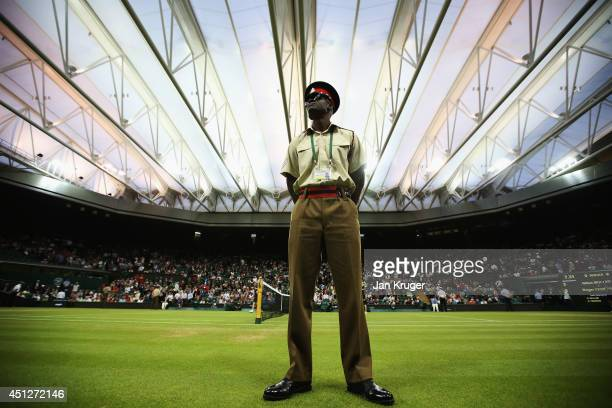 A general view of a security guard on Centre court as the roof is closed so play can continue during the Roger Federer of Switzerland and Gilles...