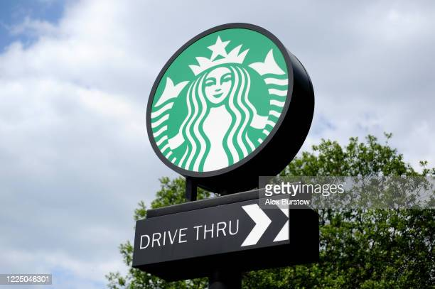 General view of a Starbucks logo seen on a sign at the entrance to a Starbucks drive-through on the day after it's re-opening on May 15, 2020 in...