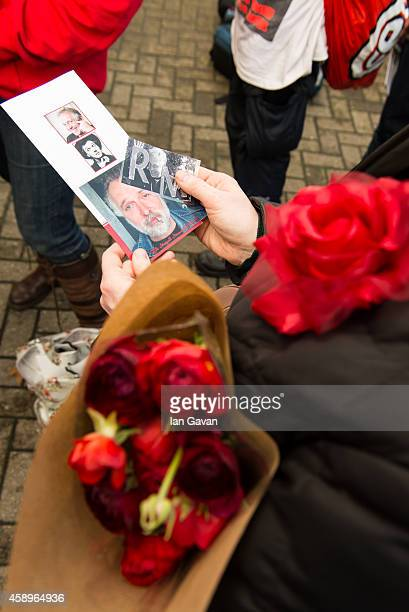 General view of a visitor holding flowers and a pamphlet as a memorial bench for the late Rik Mayall is unveiled on November 14 2014 in London England