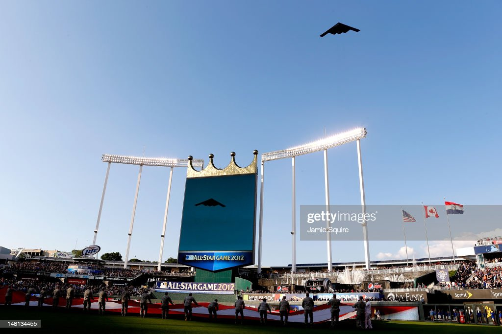 A general view of an American Flag being stretched out and help by Military Personnel as a Stealth Bomber performs a flyover during the 83rd MLB All-Star Game at Kauffman Stadium on July 10, 2012 in Kansas City, Missouri.