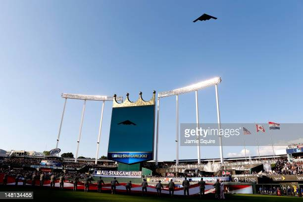 A general view of an American Flag being stretched out and help by Military Personnel as a Stealth Bomber performs a flyover during the 83rd MLB...