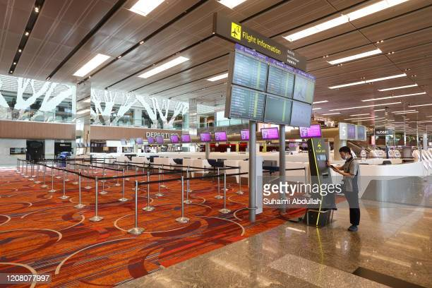 General view of an empty check in counters at Changi Airport on March 24, 2020 in Singapore. Singapore will not allow short term visitors to enter or...