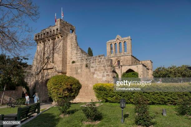 general view of bellapais monastery with tourists walking in the garden in northern cyprus. - emreturanphoto stock pictures, royalty-free photos & images