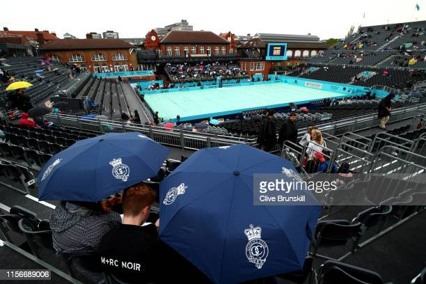General view of Centre Court as fans shelter under umbrellas due to a rain delay during day Two of the Fever-Tree Championships at Queens Club on...
