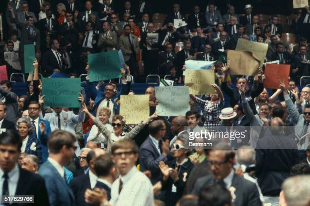 General view of Convention floor as Antiwar demonstrators carry signs 'Stop the War' 'Ending the Bombing' and 'Vote the Minority Plank'