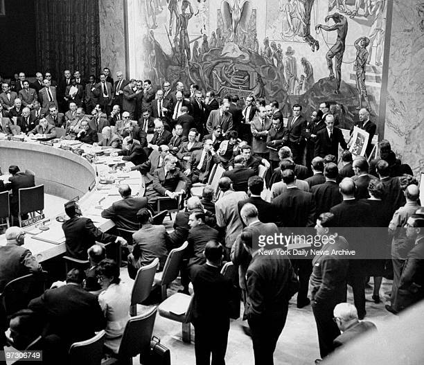 General view of delegates of the United Nations looking at a poster of the locations of Cuban missile bases.